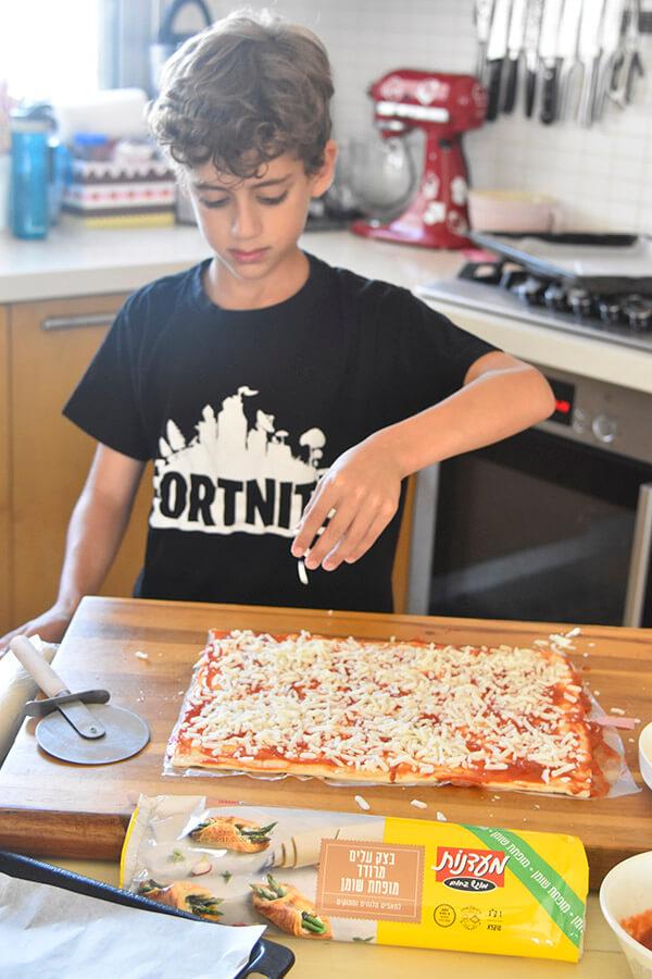 גיא מפזר גבינה על קרואסון פיצה